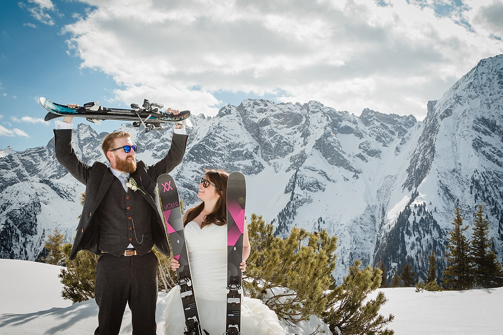 Couple pose with their skis for the ski wedding in the Alps by Wild Connections Photography